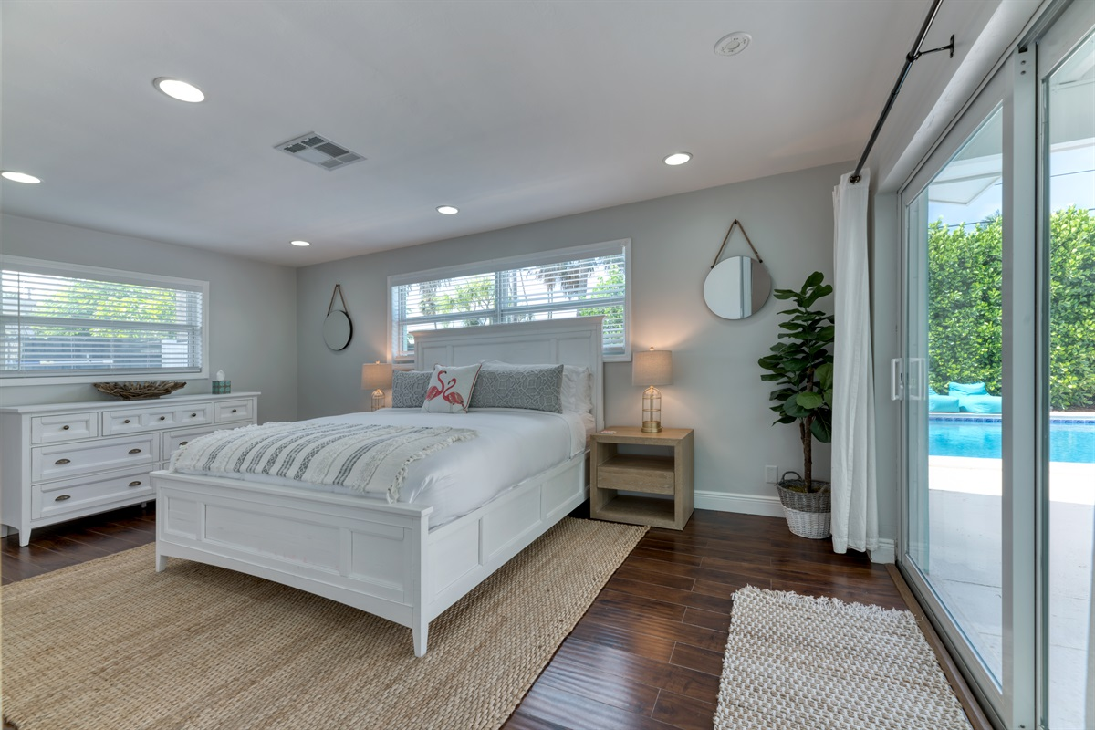 Luxurious Master Bedroom with King sized bed with crisp whites and touches of coral. En-Suite private bathroom, Smart App Roku TV and direct access onto the pool deck.