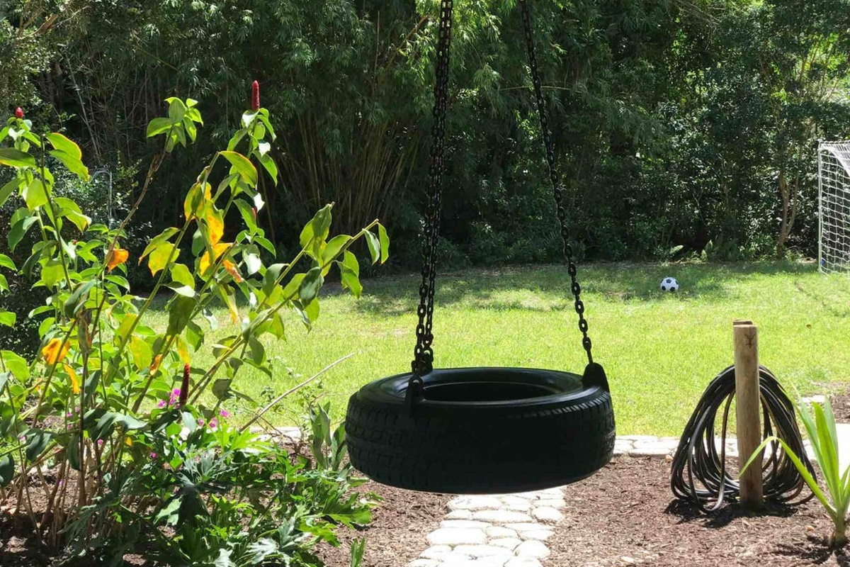 FUN TIRE SWING INSIDE THE LANAI OVERLOOKING THE FRONT YARD AREA.