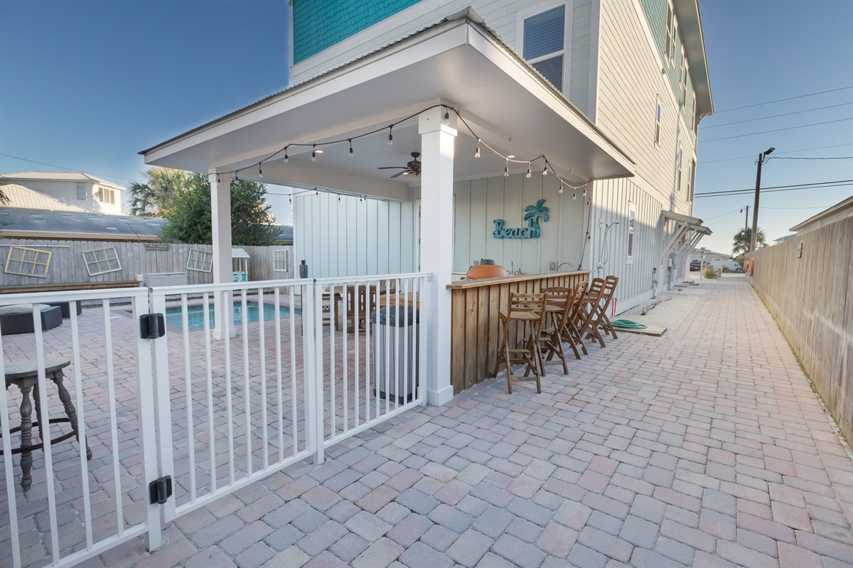 A private yard offering a complete outdoor kitchen, Kamado Joe grill, covered seating and secured with a lift gate and pool alarm to safeguard the little ones. The outdoor shower has hot and cold water to rinse the sand off after a day at the beach!