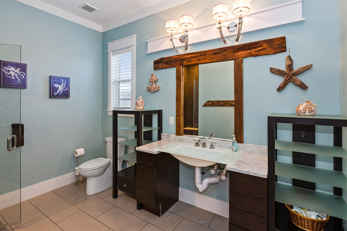 This wheelchair-accessible bathroom offers a roll under sink and roll in shower (with ramp upon request) for easy access to those who may have mobility challenges. It is a shared bath used by the first floor common area.