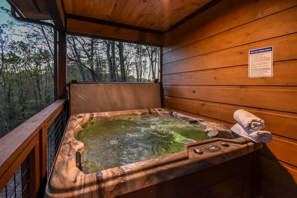 6 person hot tub on covered upper deck with views of the forest.