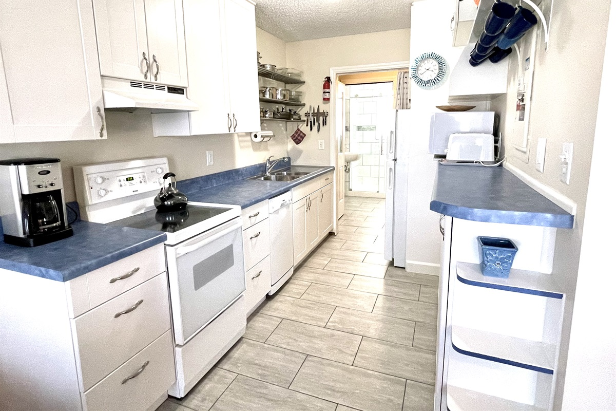 Fully stocked kitchen with all essentials plus a dishwasher. Bathroom through the doorway at the end.