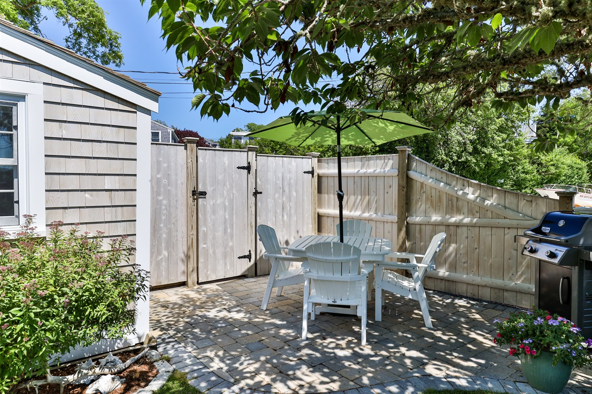 A private paver patio with a table & umbrella for four is located adjacent to the cottage with a Weber gas grill. A shady flowering cherry blossom tree provides for plenty of afternoon shade.