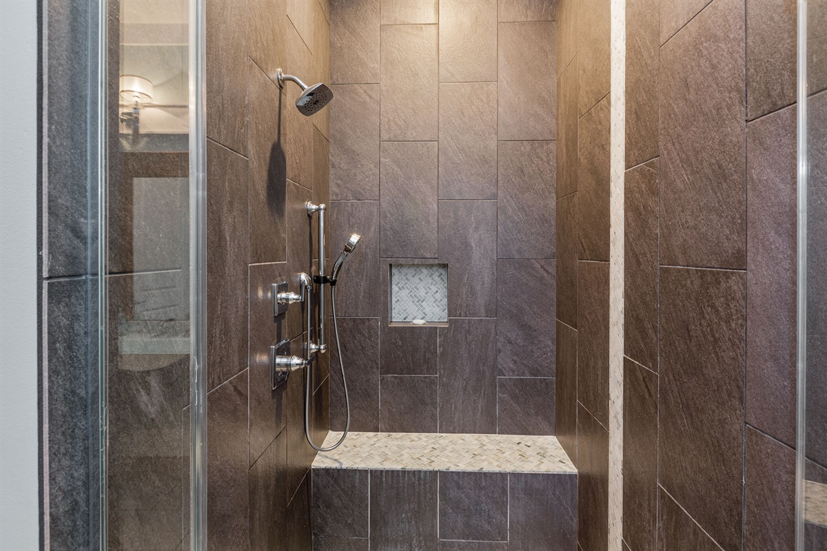 Luxurious oversized shower allows for wheelchair access and has both a stationary shower head as well as handheld shower features.