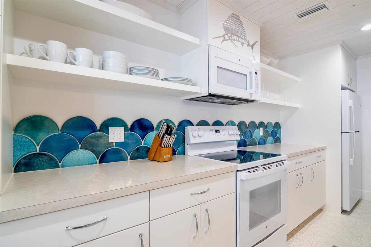 Watercolored handmade, hand glazed terra cotta tiles are the focal point of this fully stocked cottage kitchen.