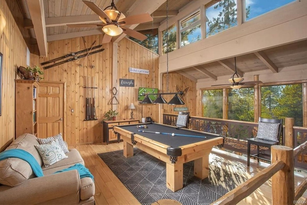 Loft Game Room: Bright and big game room features a pool table, seating, and wall of windows.