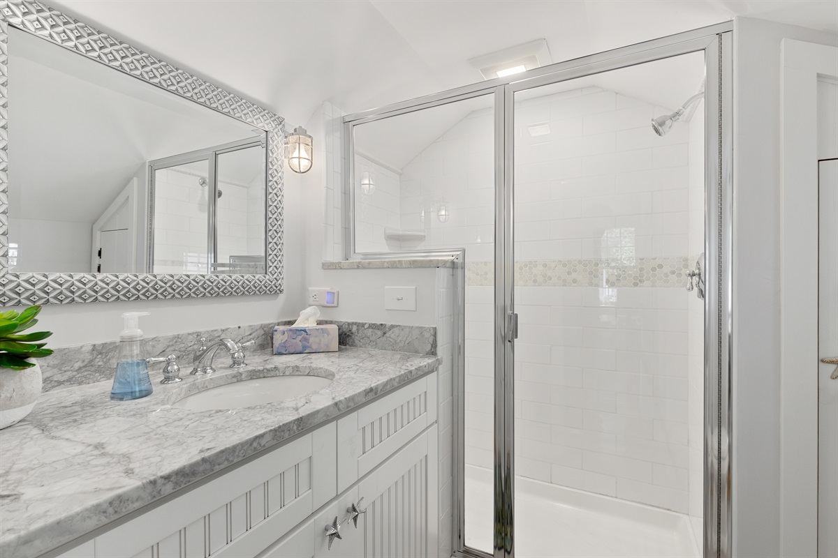 Newly renovated full bathroom with a large walk-in shower is located on the first floor. Marble top vanity and plenty of light ensure you enjoy a comfortable and airy space in a deceivingly small cottage.