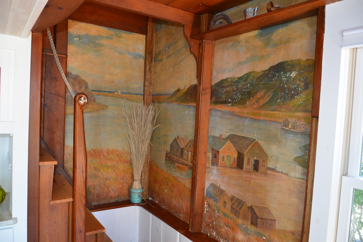 Stairwell to bunk loft with original mural depicting fishing shacks and a view of Oyster Pond facing east towards Stage Harbor Lighthouse which is still in its original location and visible from Stage Harbor. Just a short boat ride from this cottage