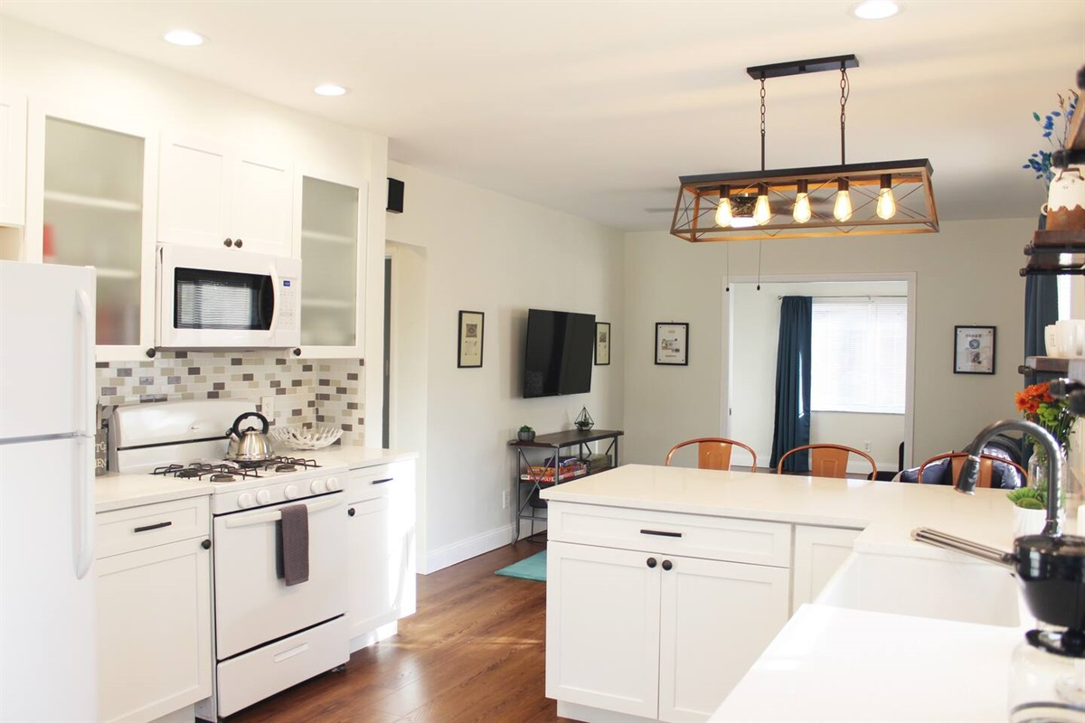 Kitchen with stove, microwave, fridge, a white porcelain farm sink and white quartz countertops.