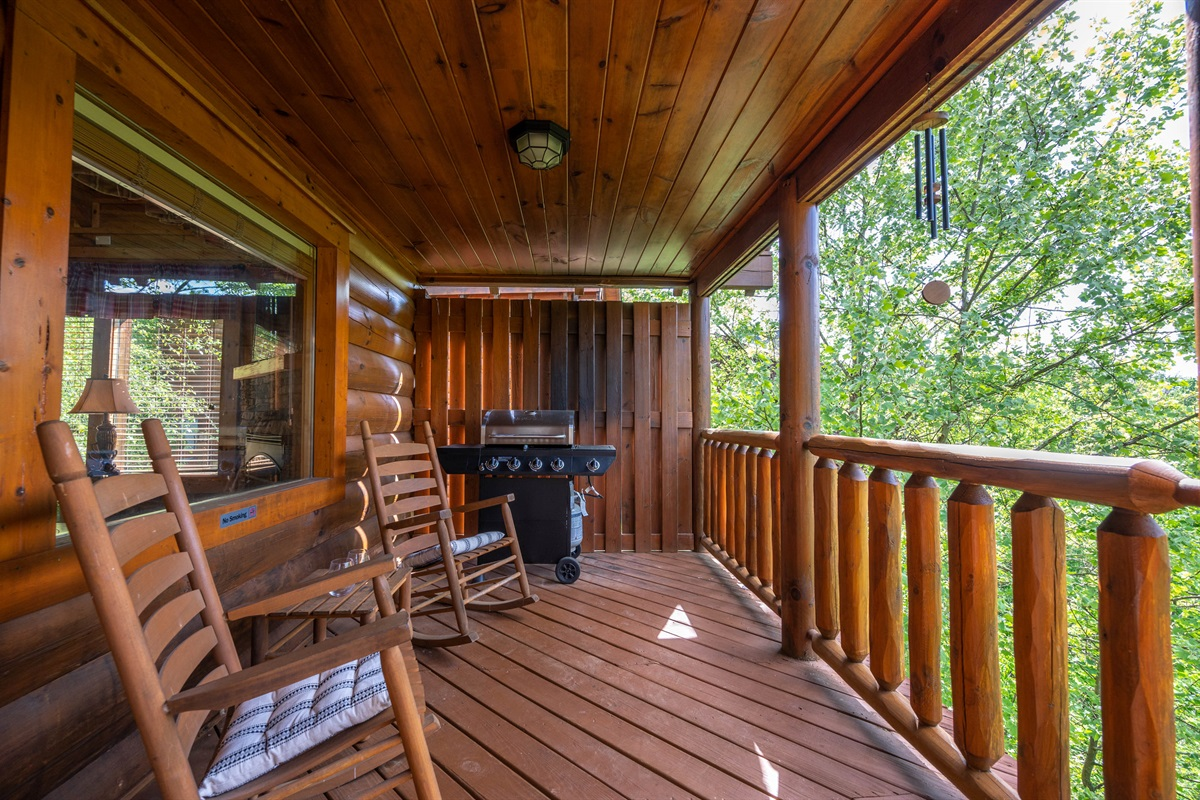 Gas grill and rocking chairs on the first floor deck.
