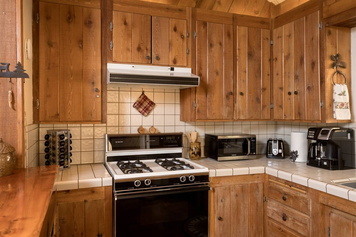 Fully-stocked kitchen with breakfast bar seating for 2, gas range, toaster, microwave, coffee maker, dishwasher, & refrigerator.