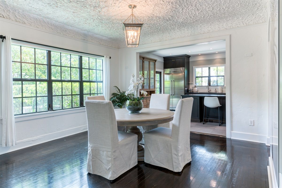 Step under the arch into the dining room area with large wooden table and high- backed fabric dining chairs. With large windows and views of the open plan kitchen. Easy access to serving.