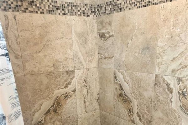 Large master shower with pebble tiled floor.