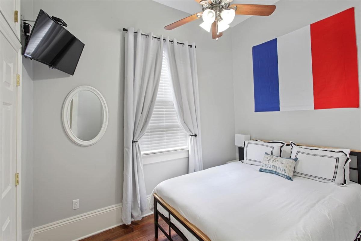"""Bedroom 2. 1 queen bed. 32"""" tv. Closet. Luggage rack."""