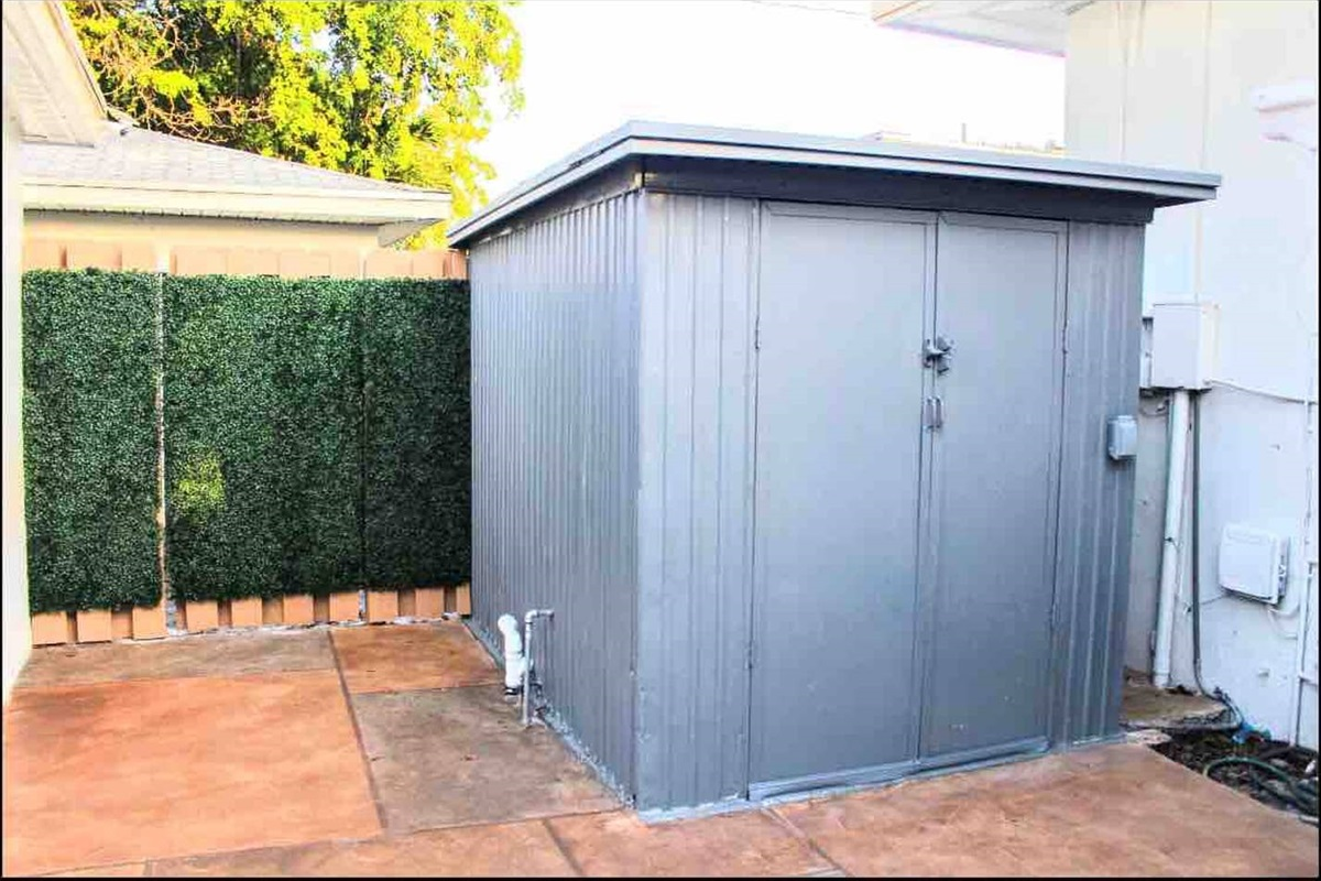 The industrial gray shed in the back patio houses a private washer and dryer inside.