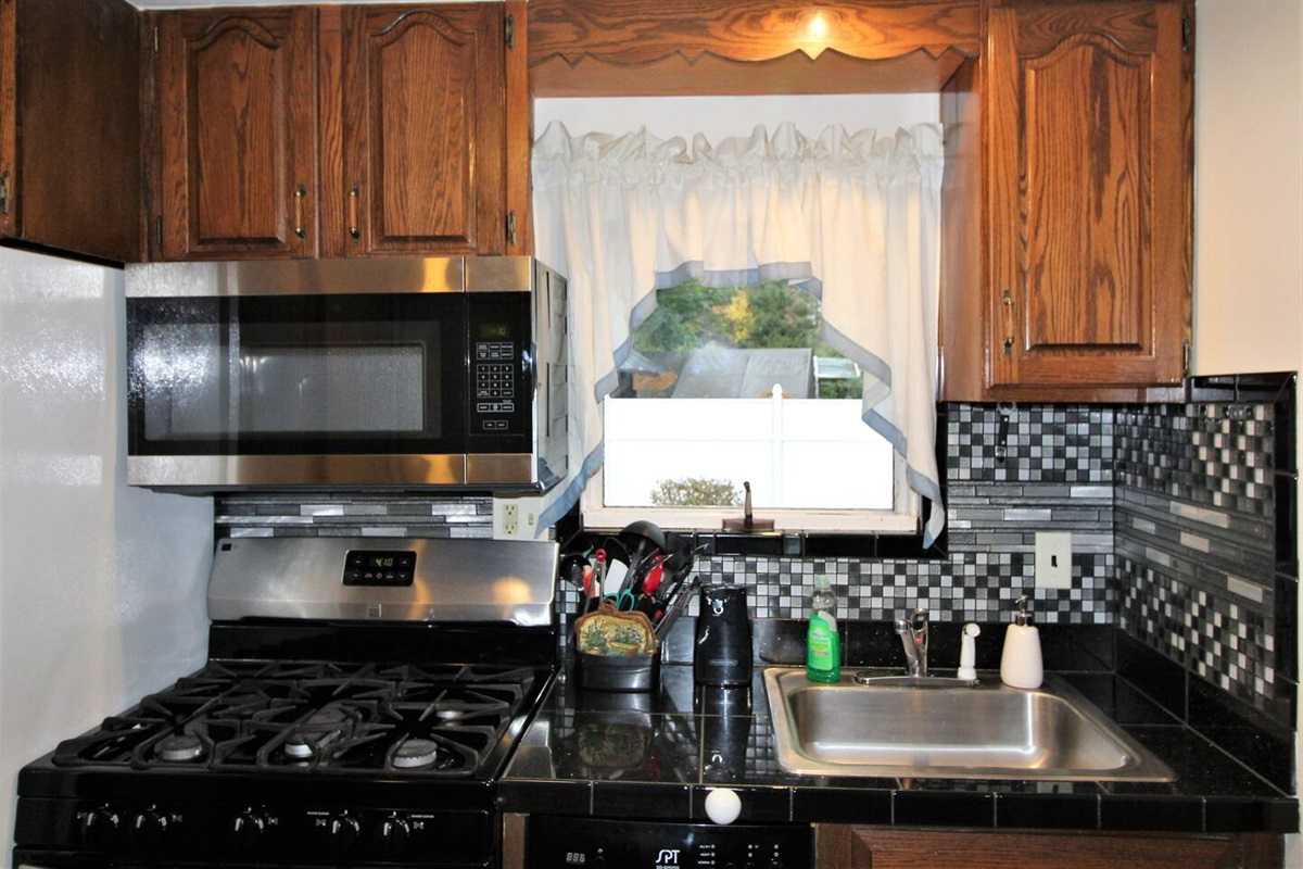 Stainless steel stove, microwave and dishwasher with a newly tiled backsplash surround.