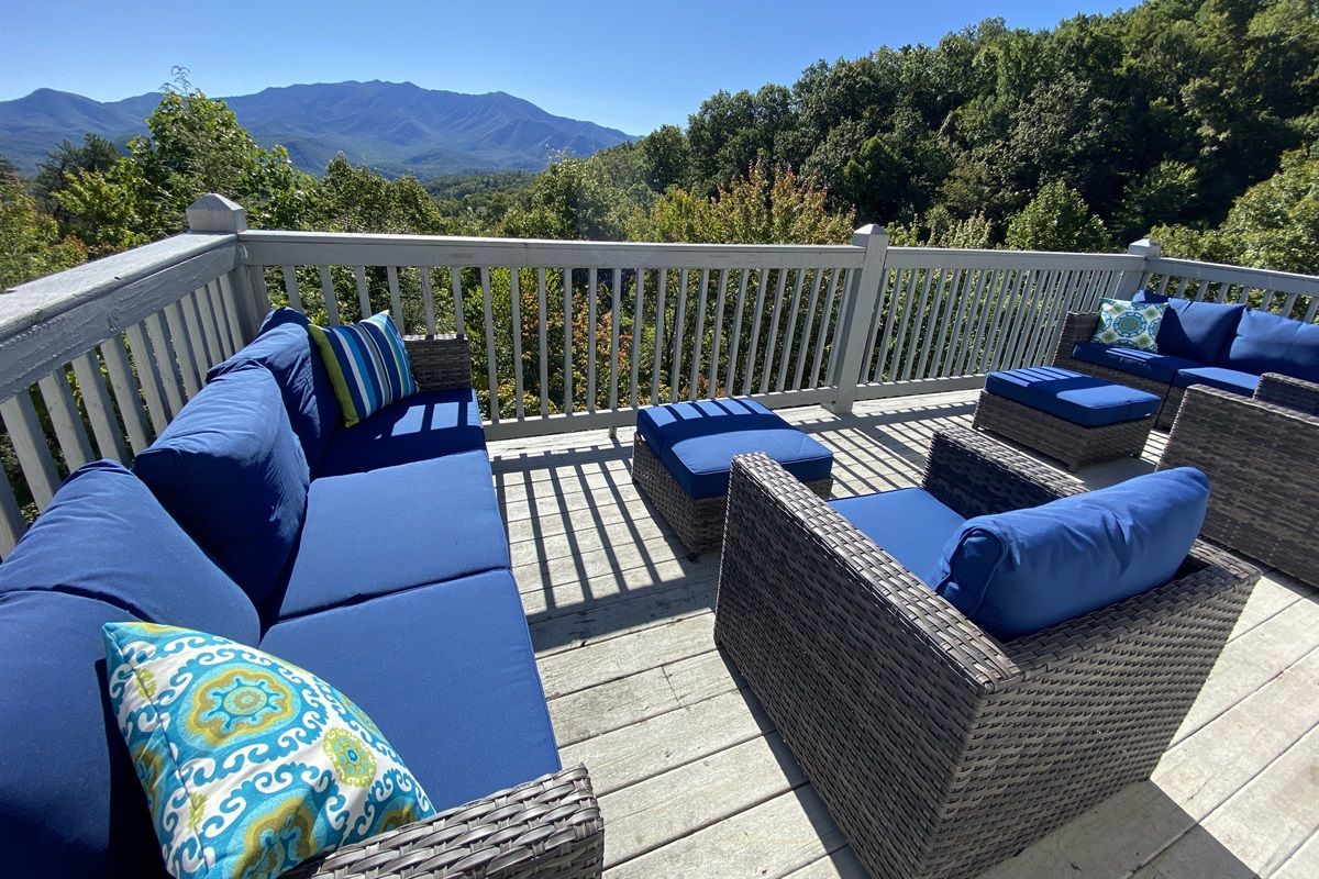 Upper deck with comfortable furniture and mountain views