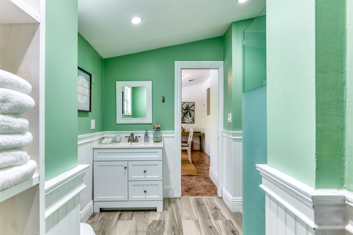 Tasteful guest bathroom with shower and beachy tones.