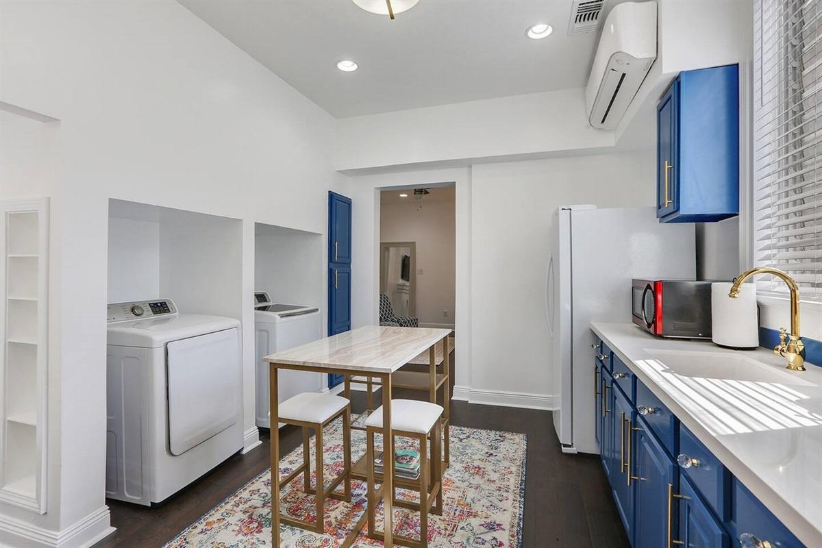 Full kitchen, laundry, door to bedroom.
