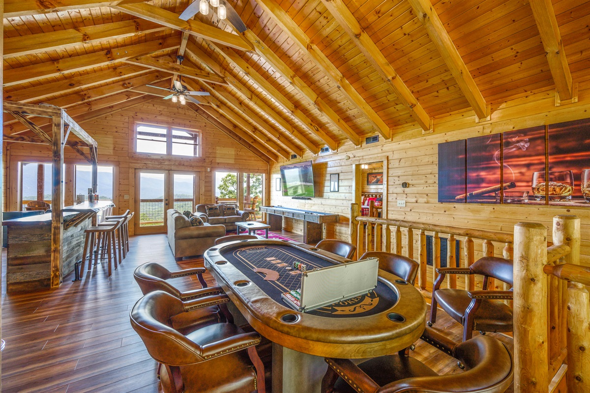 Top Floor is set up for the adults to have fun too!  Custom made bar, 80 inch Smart TV, 8 person Poker Table that also converts into a table for eating, 12ft Shuffleboard table and a Table Top Arcade Game with +4,500 games!