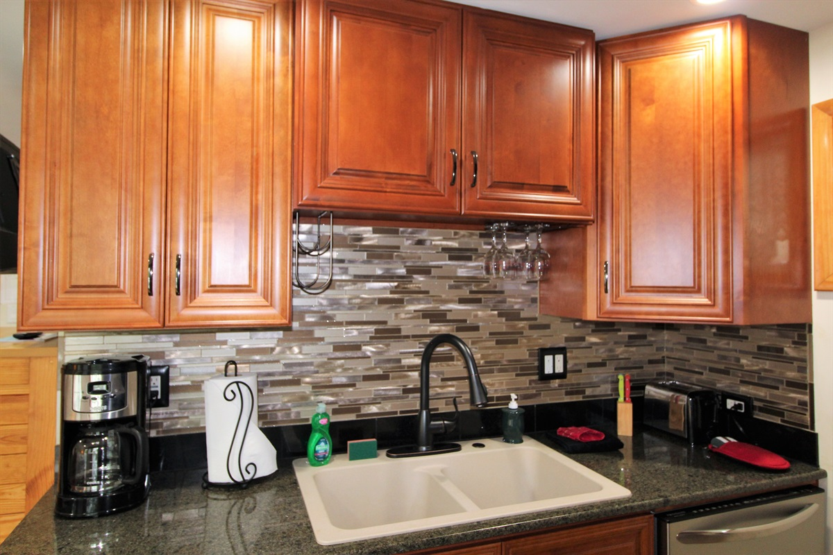 Wet bar in the upper level suite with newly tiled backsplash, dishwasher and microwave (not pictured)
