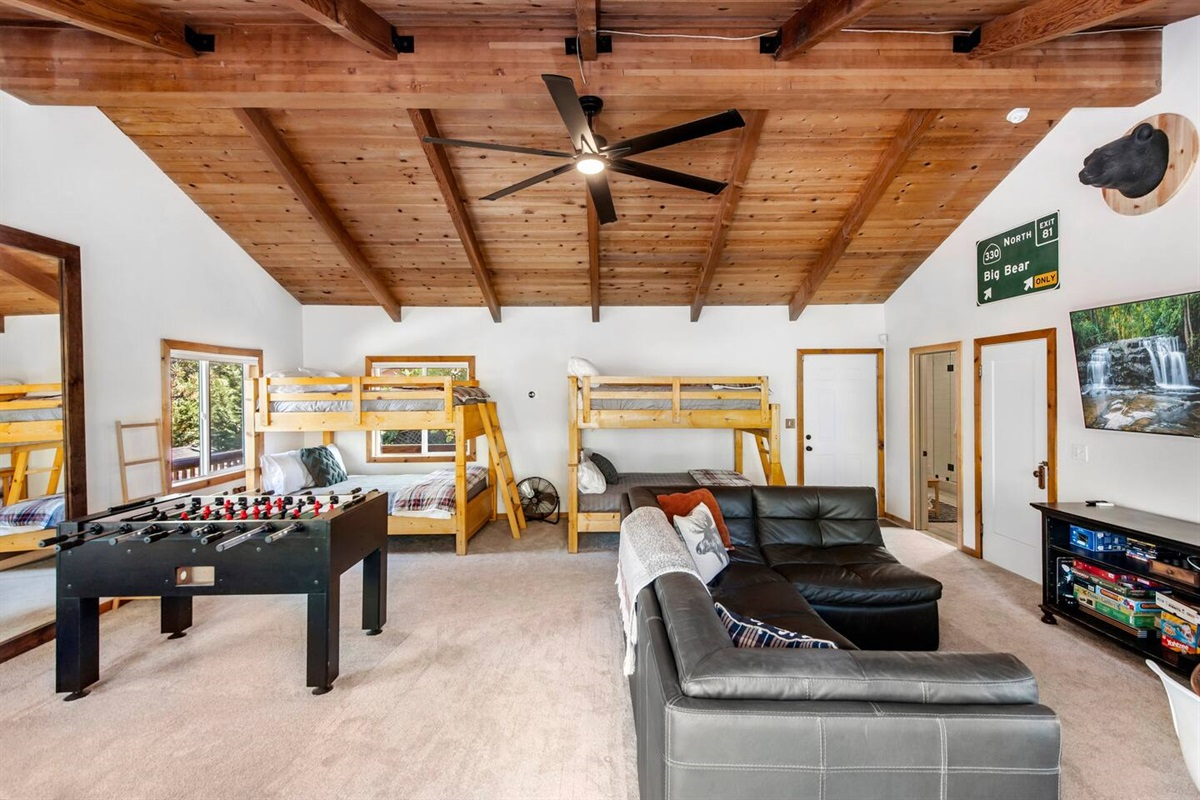 """Bedroom #1 (Lower Level): Spacious bedroom with 6 beds to sleep 8 people, foosball, and 65"""" Roku smart TV with cozy sitting area."""