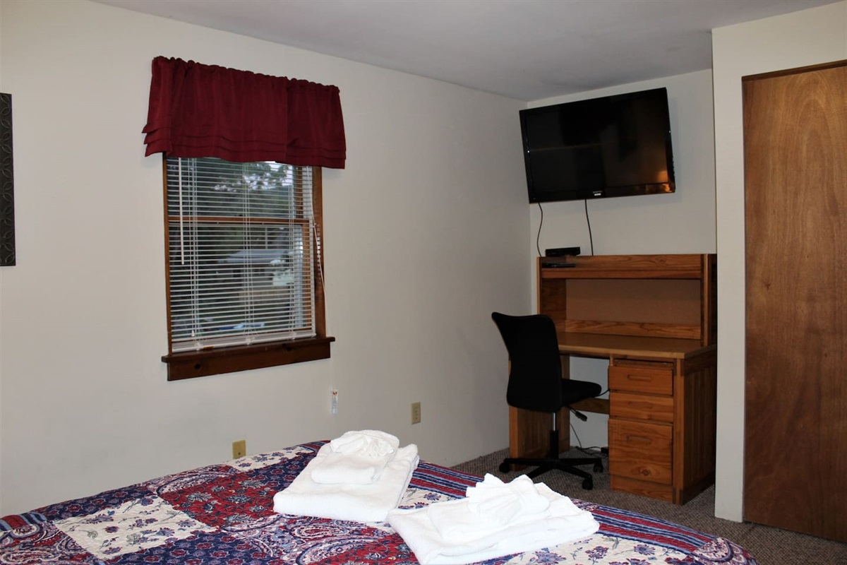 Large wall mounted TV and workspace for your laptop in queen bedroom