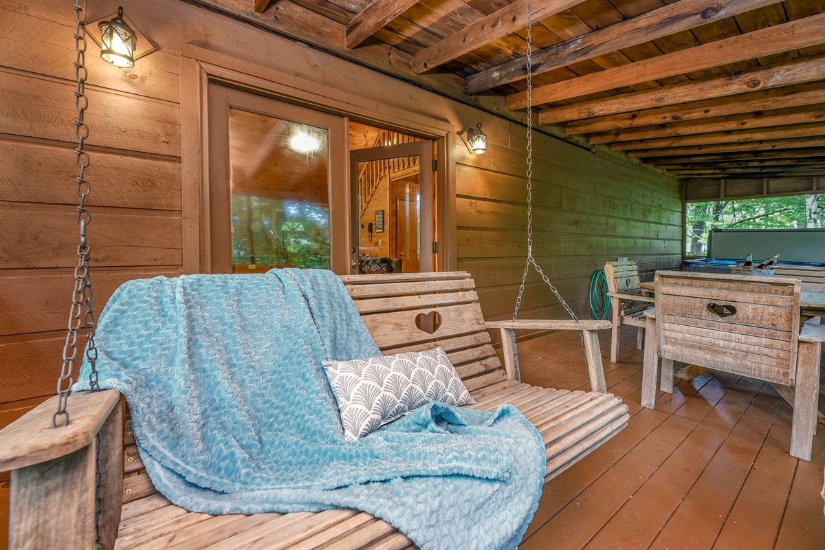 The main level deck has ample seating with a porch swing and hot tub!