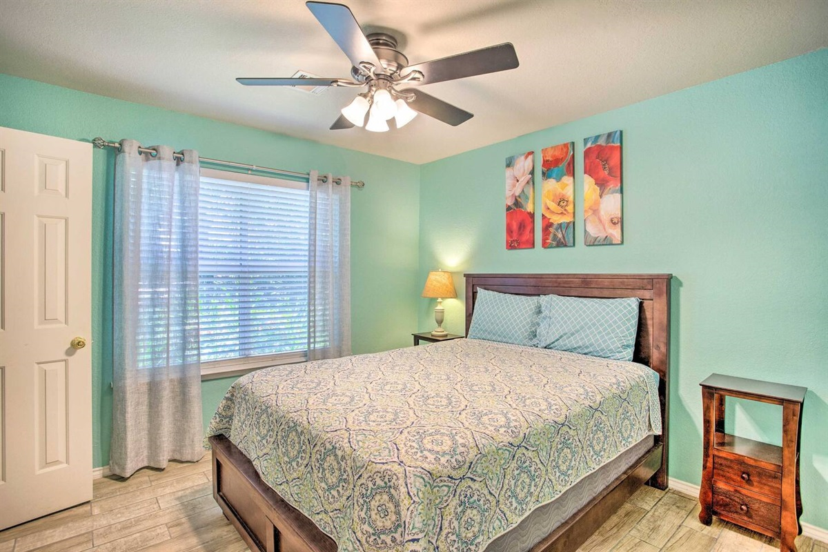 Master bedroom with queen size bed, walk in closet, and attached bathroom.
