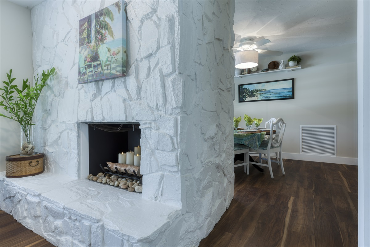 We love this unique stone textured wall with built in remote controlled candle fireplace leading into the intimate 6- seater dining room with charming tablescapes and work desk for the remote workers or virtual students.