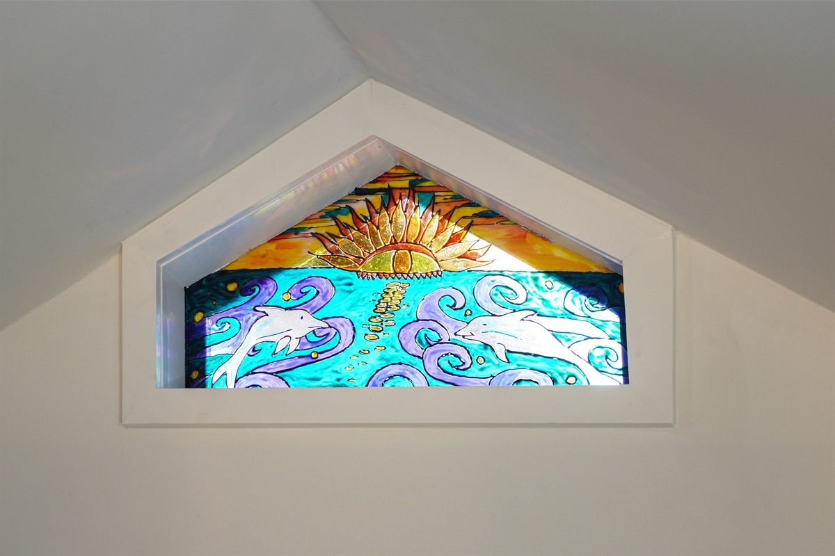 Hand-painted gable window sends rainbows of light onto the walls when the sun hits it