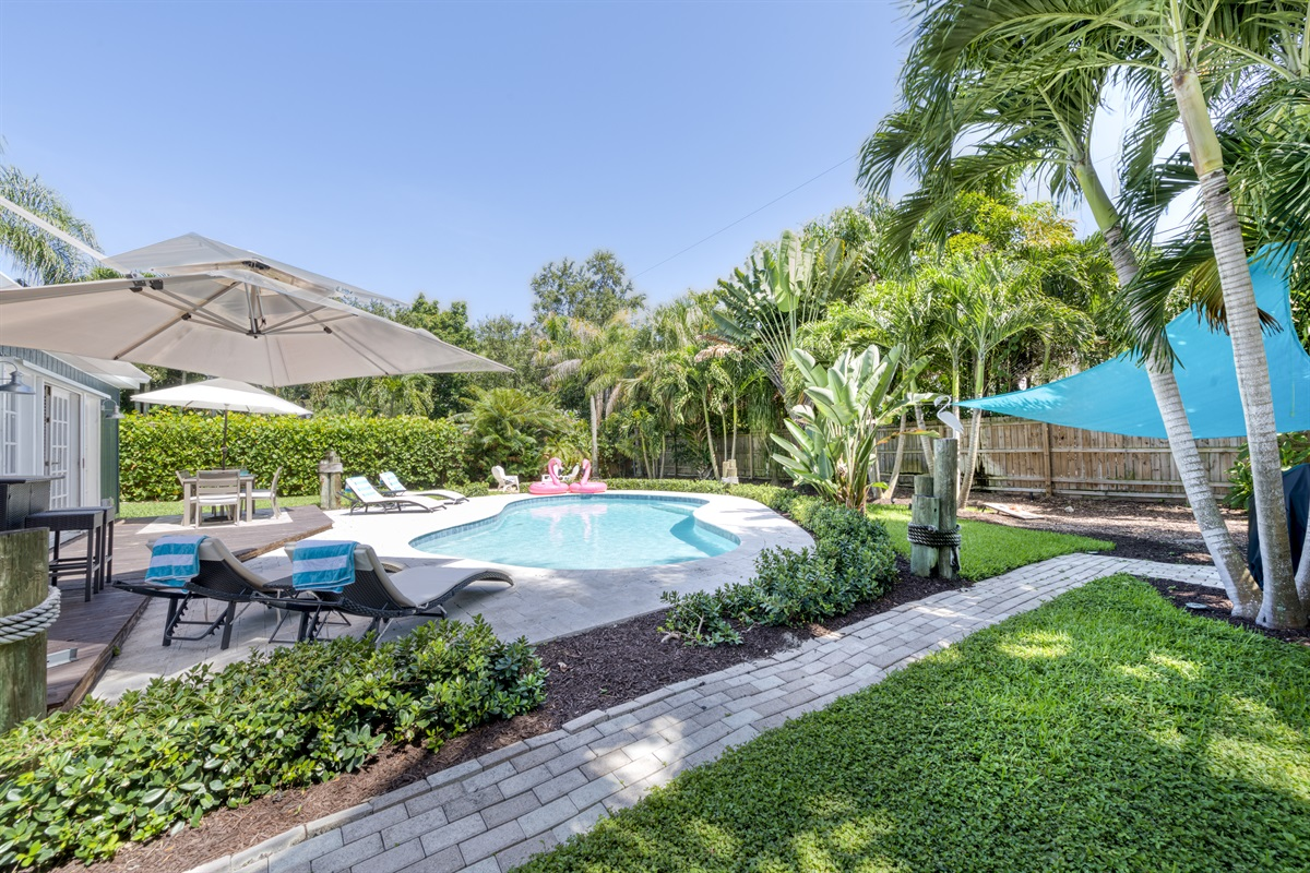 Relaxing family friendly 3-bedroom & 2-bathroom Villa situated between Palm Beach and Jupiter features a large, tropical, outdoor entertainment space with large pool, BBQ Gas Grill, patio dining and lounging and Cornhole