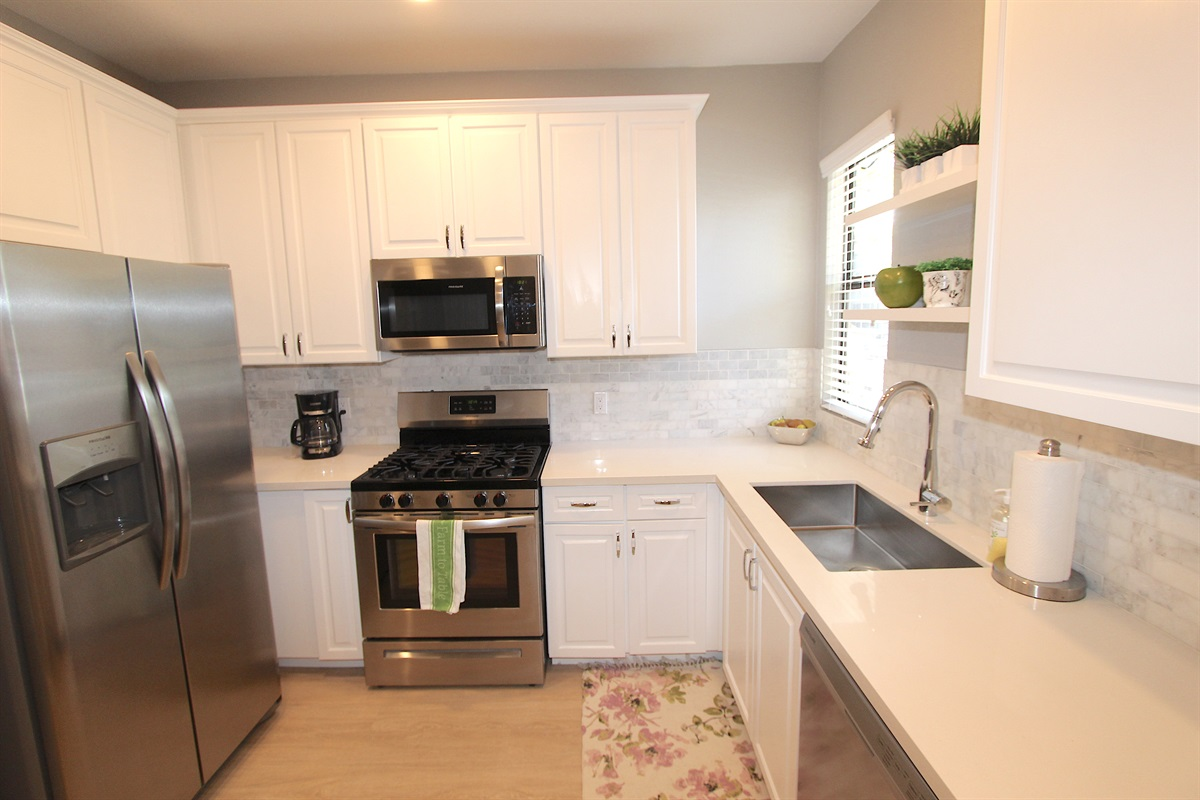 Kitchen with stainless steel appliances, quartz counters.