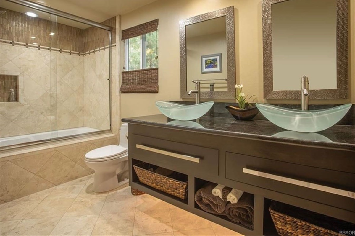 Bathroom #1: It features dual sinks and bathtub / shower combination.