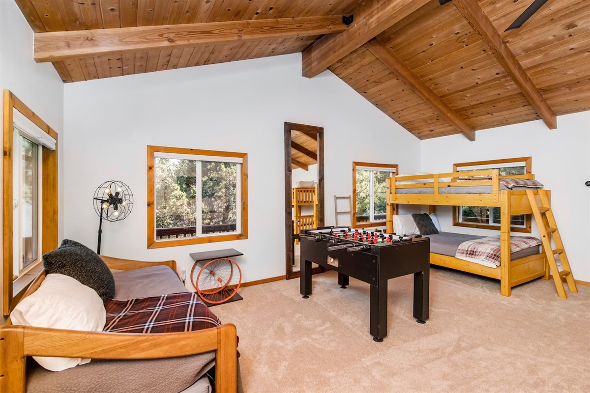 Bedroom #1 (Lower Level): Large bedroom has 6 beds to sleep 8 people, foosball table, and dedicated game table.