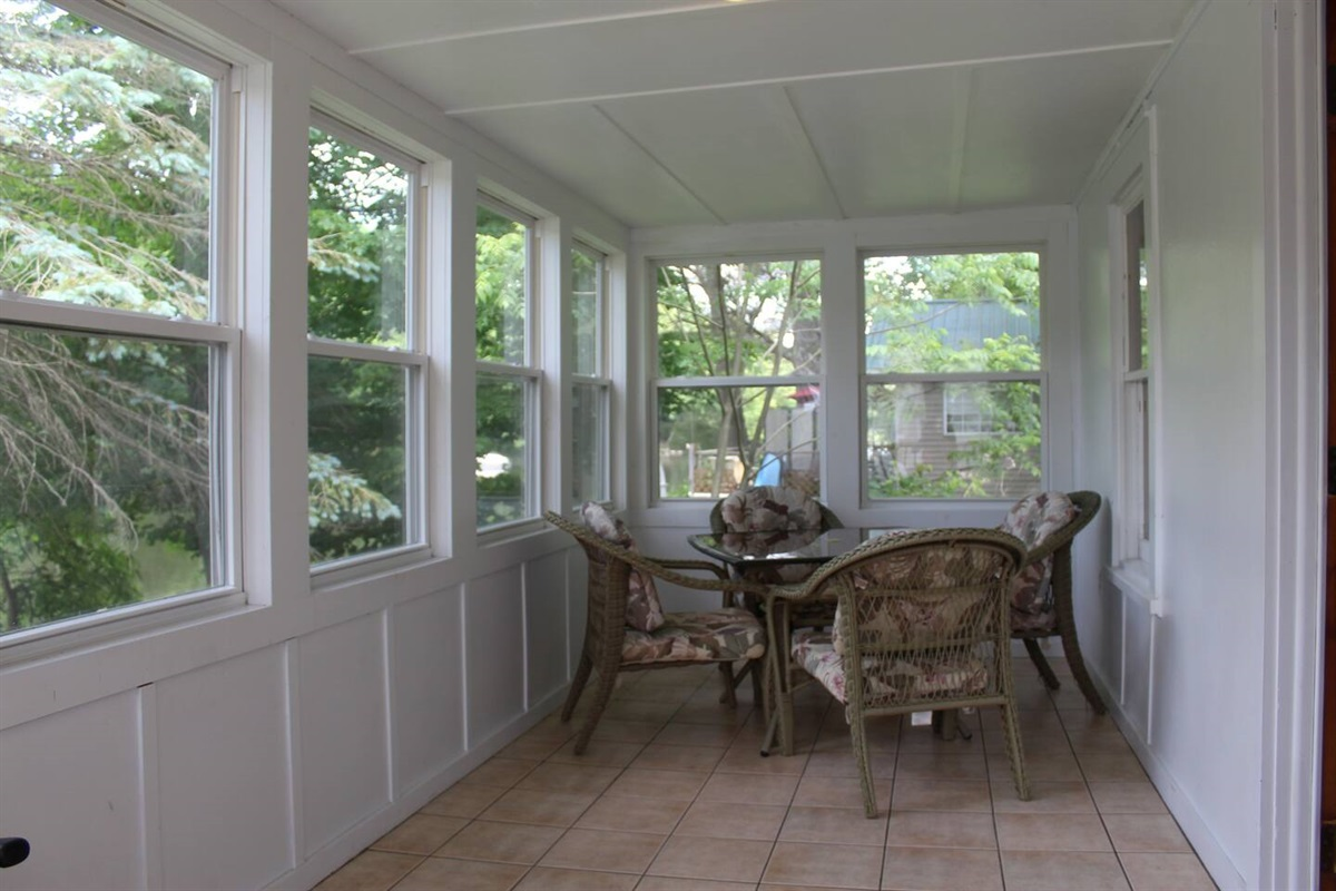 Spacious porch, with tiled floor and windows all around to enjoy the view