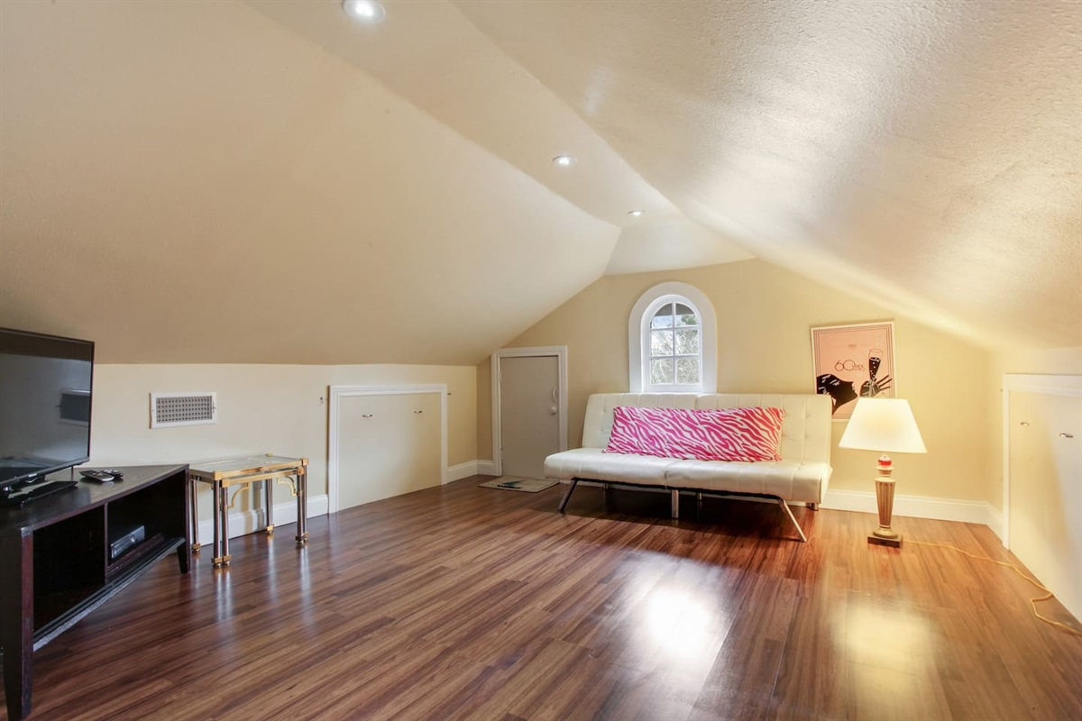 """Upstairs living/play room. Full size futon couch. 40"""" tv. DVD collection."""