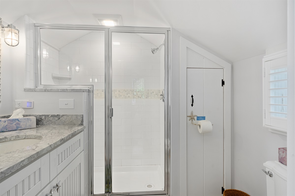 Subway tiled walk-in shower with shelf for your personal items. A new bath exhaust fan and light ensure a steam-free exit from your shower.