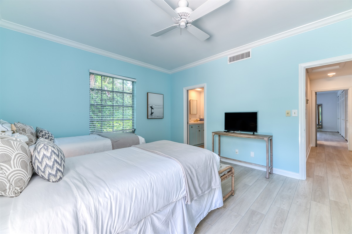 2nd Bedroom with two Twin XL beds, gorgeous light blue hues with clean whites and rustic browns. Smart App TV with stunning views of the pool deck. The room has small en-suite bathroom.