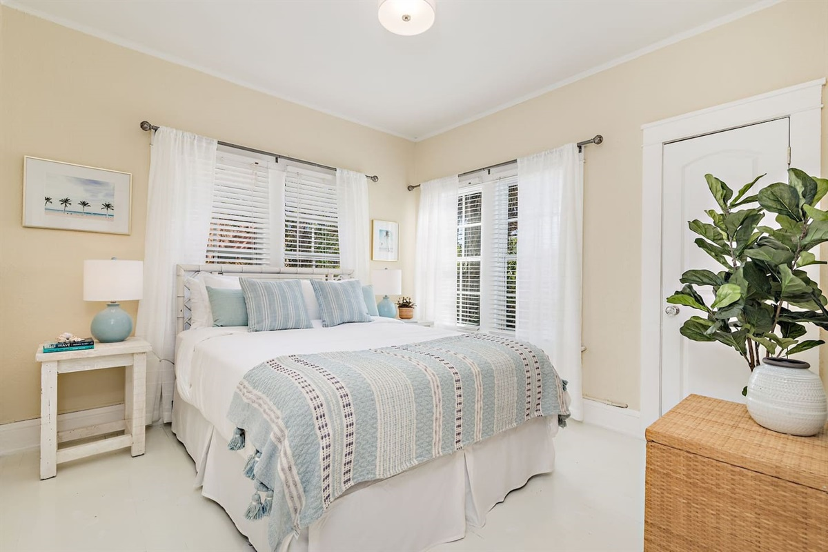 The 1st bedroom features a Queen sized bed with creams and blues. Large Smart App TV in and closet. Loads of natural light fills the room.