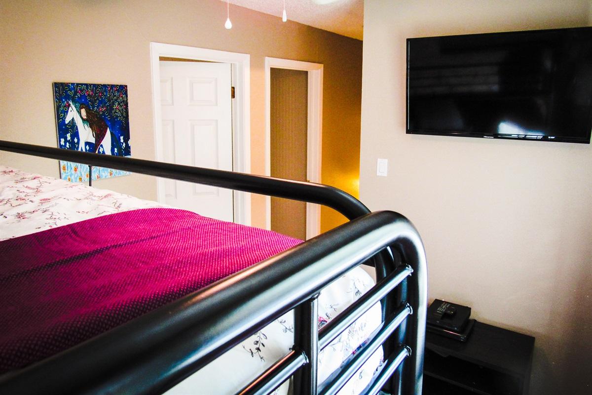 Loft w/ set of bunk beds and mounted flatscreen TV.