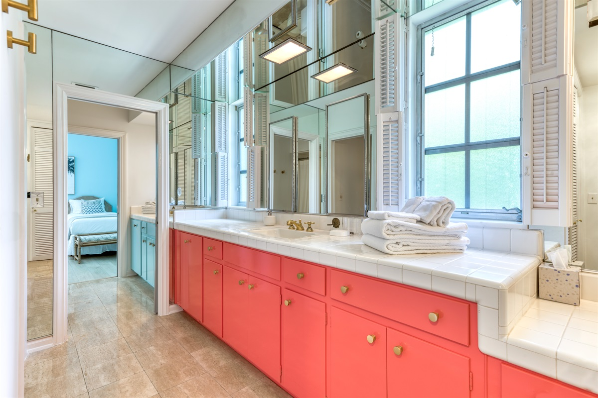 Large Master bedroom bathroom with pink vanity and white counter tops with gold fixtures and large mirrors. The bathroom has a combination tub/shower.