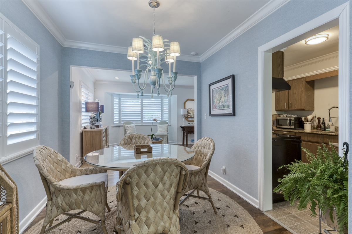 The dining room has a coastal Serena and Lily chairs and small bar display. The windows bring in the warm natural light, perfect dining area.