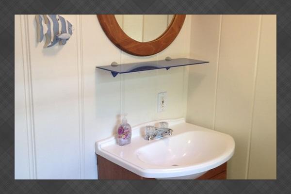 Main level bathroom vanity, hair dryer and various basics tucked under the sink!