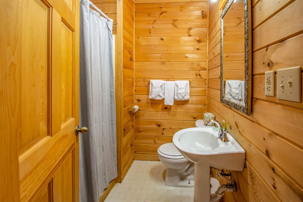 Bathroom attached to bedroom with the log bed.