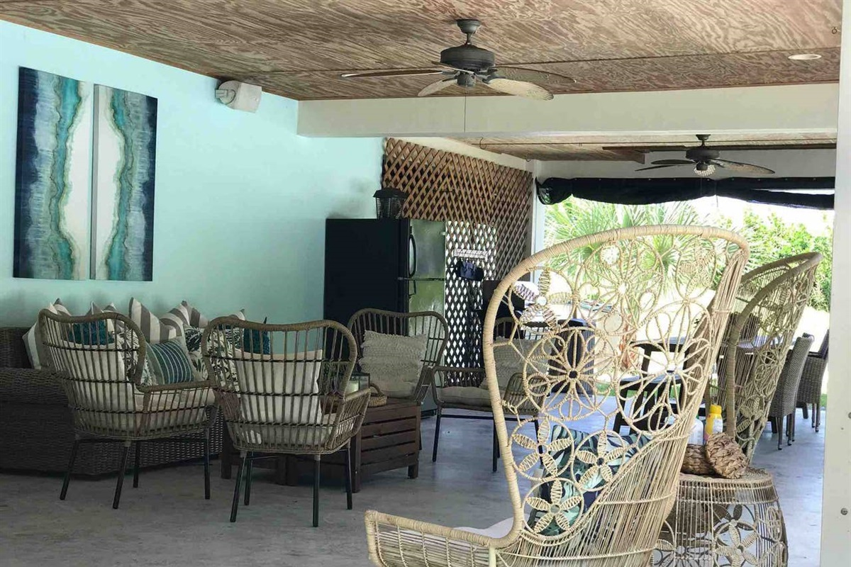 LANAI  AREA WITH OUTDOOR GRILL, REFRIGERATOR, DINING TABLE, SEATING AREAS AND SWING RIGHT OFF THE POOL AND FRONT YARD FOR OUTDOOR FUN AND GATHERING.