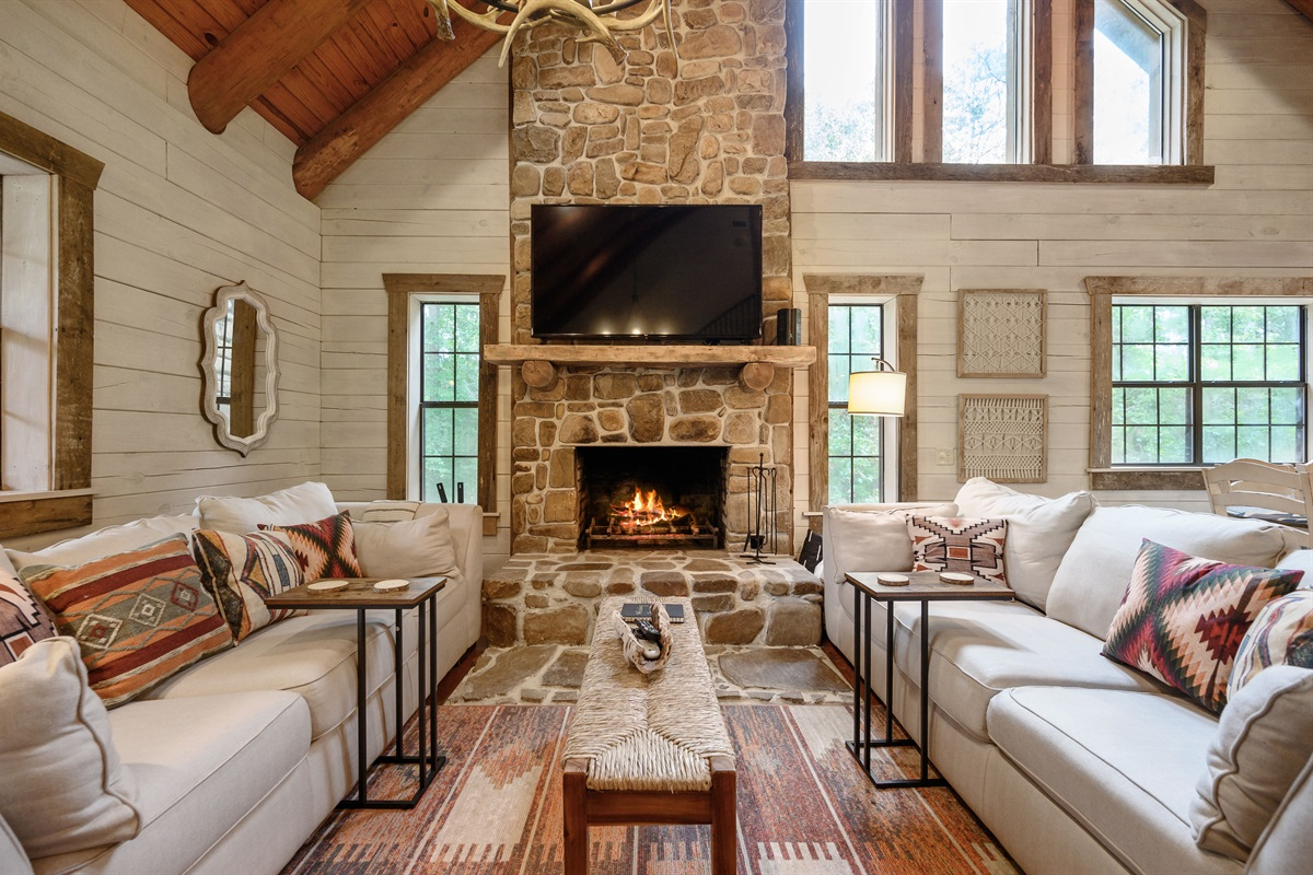 """Cozy living area with real wood fireplace and 65"""" smart TV with DirecTV"""