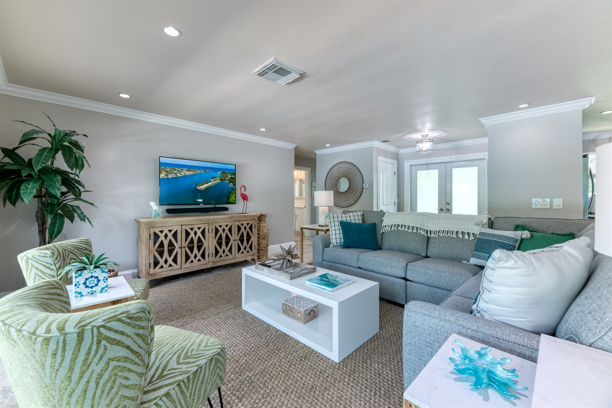 Bright & inviting living room with large L-shaped sofa, tasteful arm chairs, large Smart App TV and direct views and entrance to the amazing pool area.