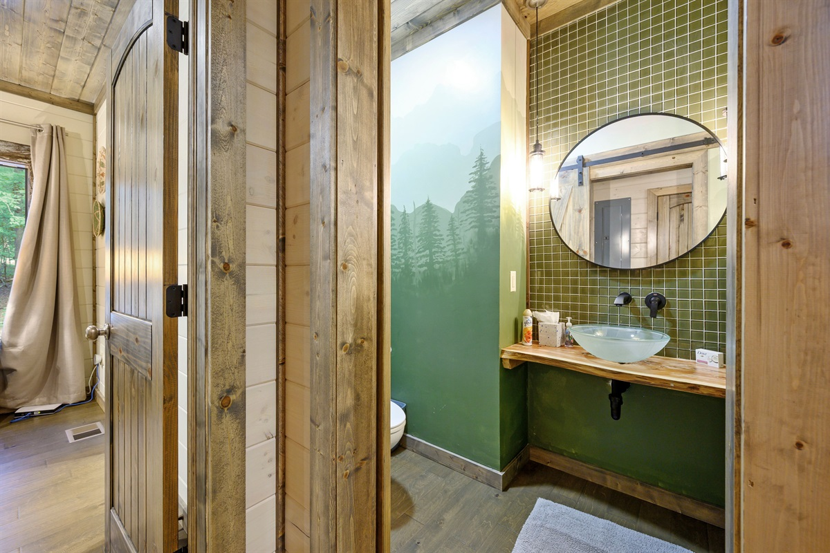 Powder bath is uniquely done with custom painted walls and barn door