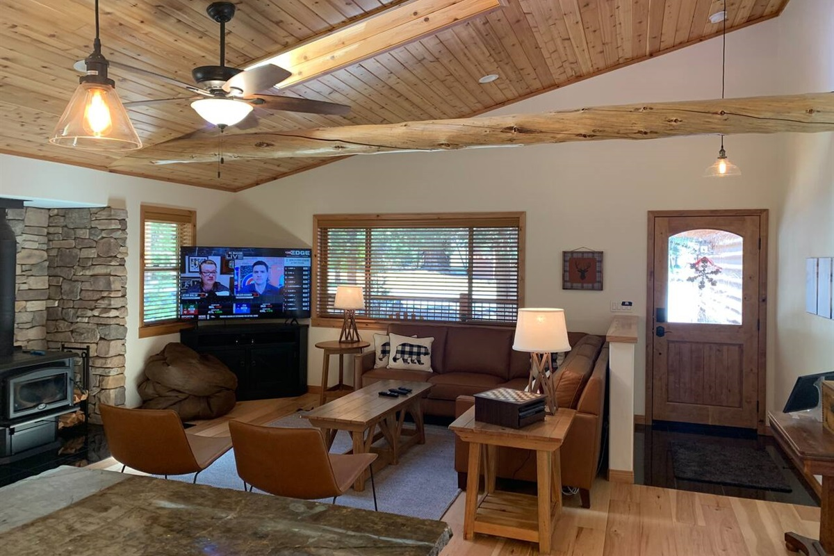 Cozy living room with large flat screen TV and wood stove.
